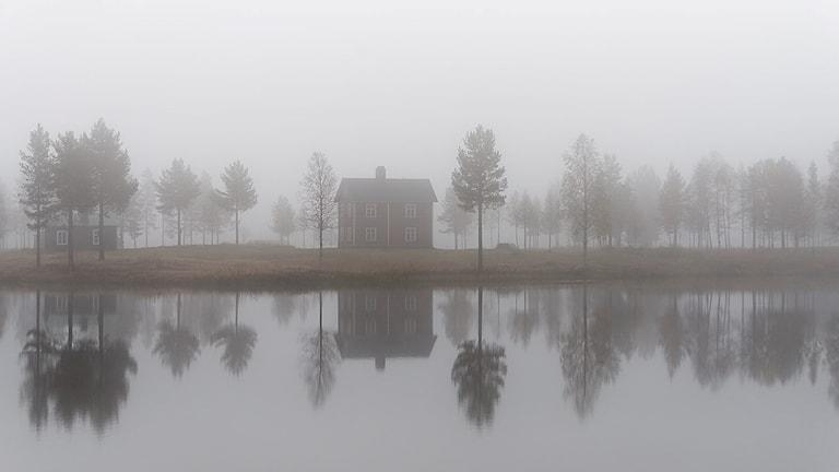 Ett gammalt hus i dimma speglas i vattenytan.