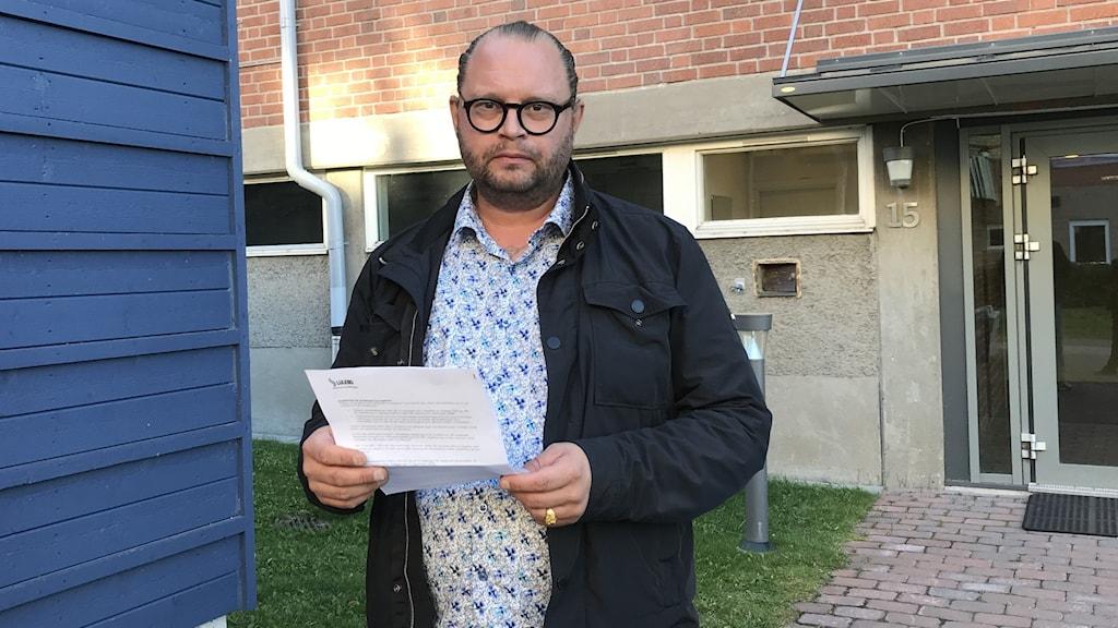 Michael Lyckhagen hyresgäst hos Lulebo. håller i ett besked från hyresvärden men ser fortfarande missnöjd ut.
