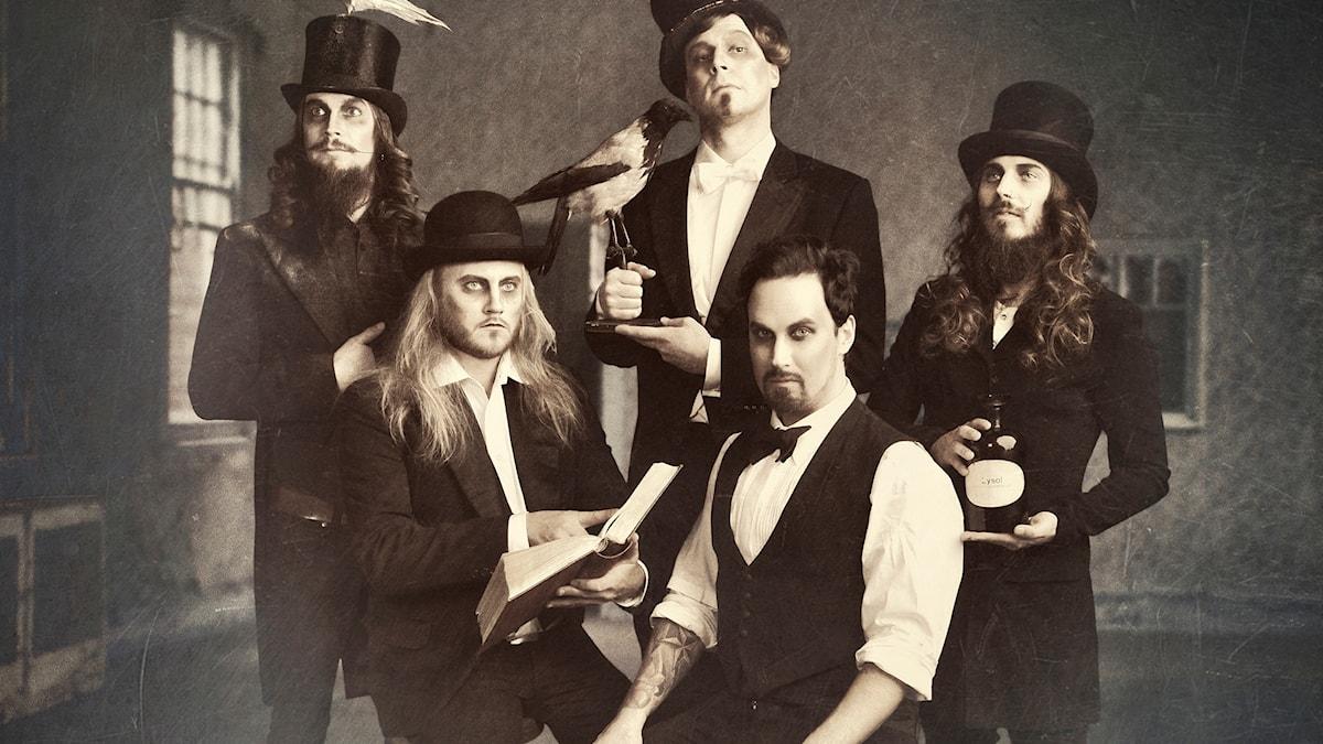 Tyyliteltu mustavalkoinen valokuva, jossa Uniklubi-bändi vanhanaikaisissa asusteissa. Kuva: promootiokuva/Warner Music Live
