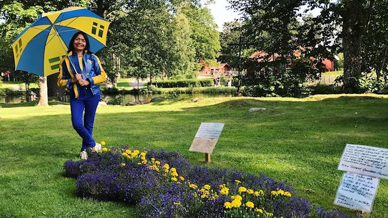 Eunice Vidals klädd i blått och gult framför sitt konstverk Helig Jord.