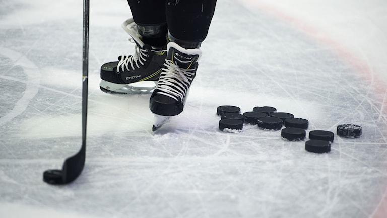 Skridskor på en hockeyspelare och en hög med puckar.