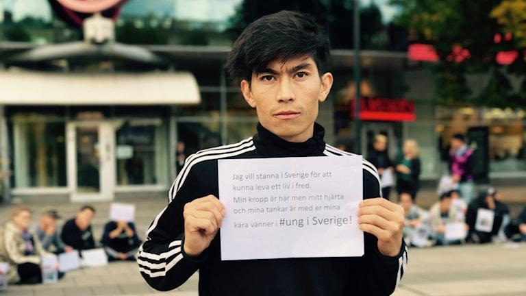 Mohammad Taqi håller i ett plakat med texten jag vill kunna stanna i Sverige för att leva i Fred.