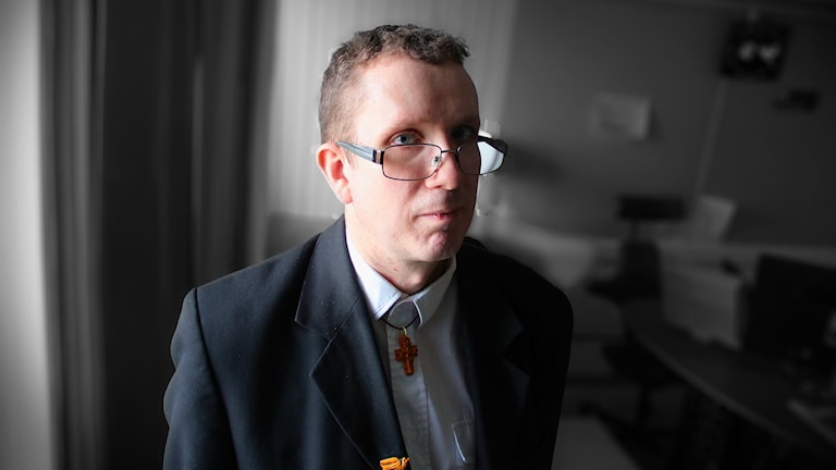 Rolf Östlund vid fönstret i P4 Gävleborgs studio. Han bär en mörk kavaj och vit skjorta med ett träkors runt halsen. Han har ljusbrunt, lite lockigt kort hår och glasögon.