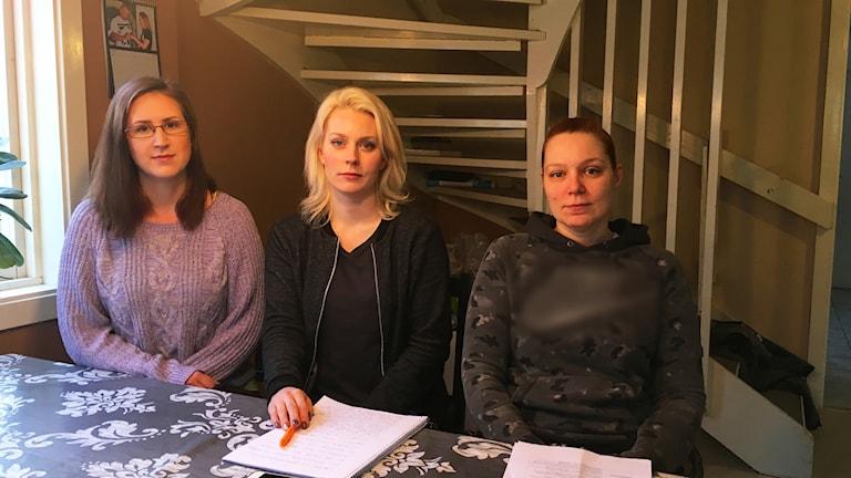 Tre föräldrar sitter vid ett bord i ett kök med papper framför sig.