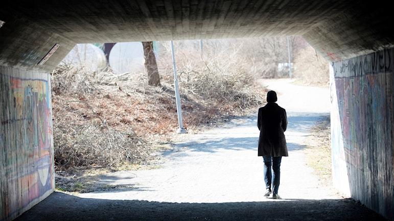 en ensam person i trenchcoat och huvudbonad i en gångtunnel