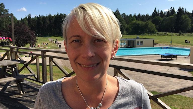 Ljus kvinna utomhus med badbassäng i bakgrunden.