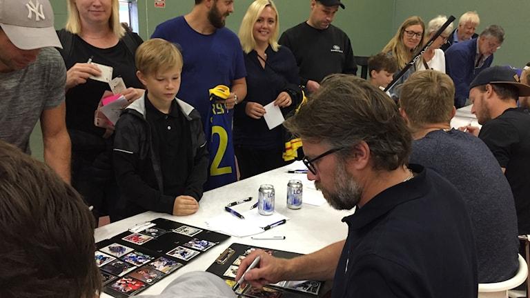 Peter Forsberg skriver autografer till sina fans.