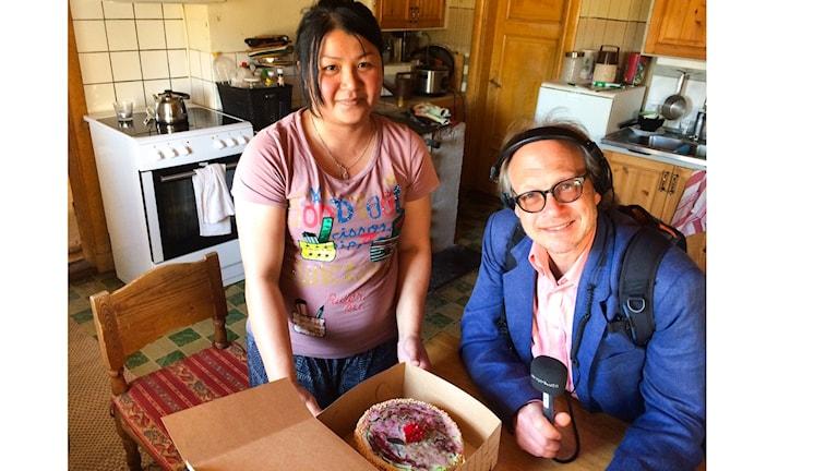 Två personer i ett kök i Delsbo. Den ena sitter (Larry) och har hörlurar och en mikrofon. Den andra står och håller i en tårta hon precis fått.