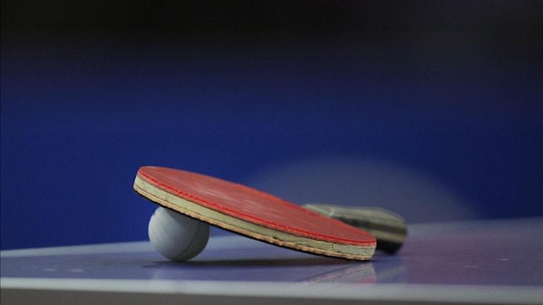 Ett pingisrackert som ligger med en boll på ett pingisbord