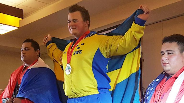 En glad Joel Sundelin med guldmedaljen runt halsen.