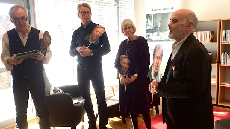 Fyra av jurymedlemmarna i Dagermansällskapet står på rad med skyltar föreställande 2017 års Dagermanpristagare, Anders Kompass. Dom har alla mörka kläder och lyses upp bakifrån av solen igenom dom stora fönstren som finns i Stig Dagerman-hörnan i biblioteket på högskolan i Gävle.
