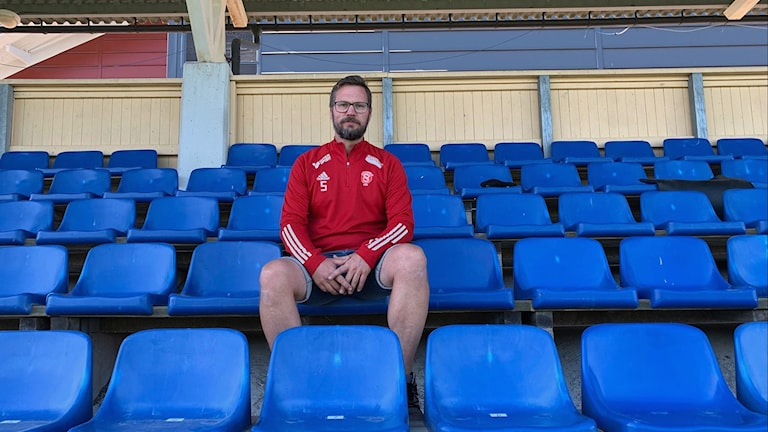 Anders Eriksson sitter på en läktare med blå stolar.