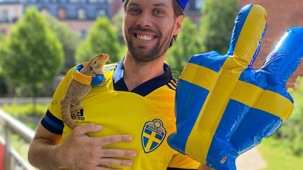 En man i Sverigetröja med en ödla på axeln.