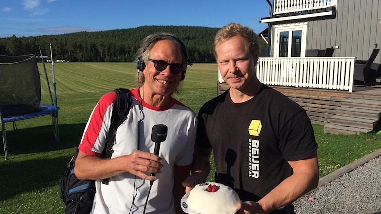 Larry Forsberg pratar med Henrik som står med tårtan i handen