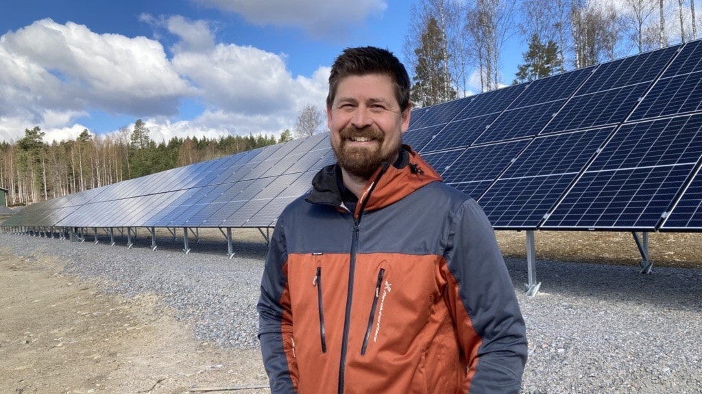 En nöjd man framför en solcellspark i centrala Bollnäs.