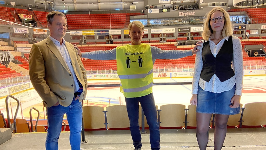 tre personer i en ishockeyrink