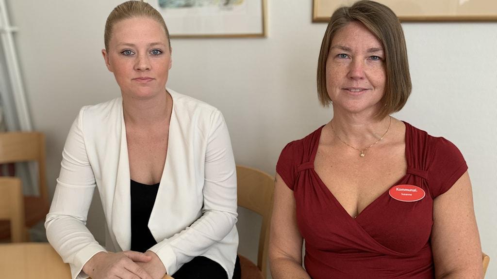 Två kvinnor sitter bredvid varandra. En har en vit kavaj och den andra en röd blus.