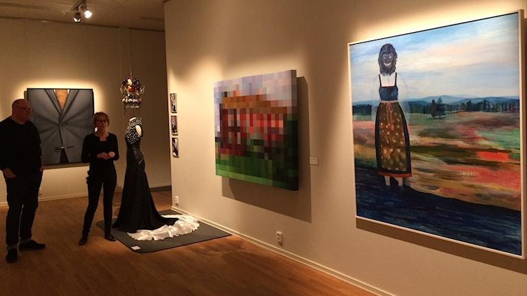 Anders Johnson och Ingela Broström framför några konstverk i en av utställningsalarna på Länsmuseet.