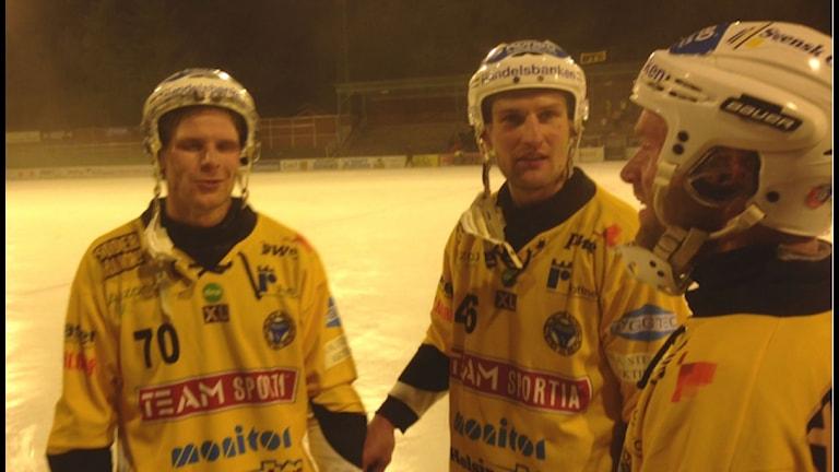 Ilari Moisala och Robert Dammbro (närmast) gratulerar nummer 70, Rolf Larsson, till sina tre mål. Foto: Christrian Höijer/Sveriges Radio
