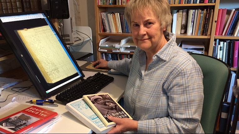 Elvi Sandberg med första utgåvan av Hälsingerunor från 1921 och senaste med Snoddas på omslaget.