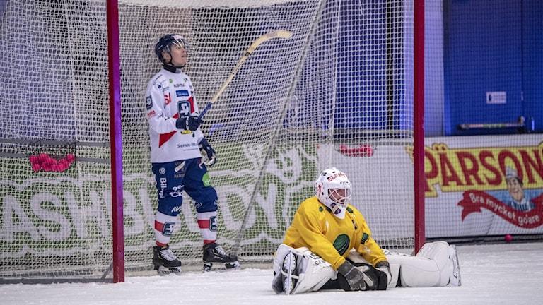 Spelare som är synligt besvikna, bandymålvakt sitter på isen.
