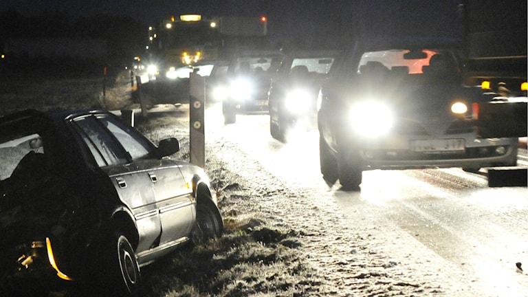 Bilar på en snöig väg. En bil i diket.
