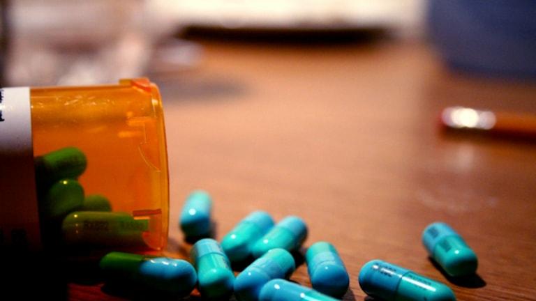 En bild på blåa piller i en orange burk.