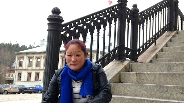 Majs Keller, ordförande i RFSL Hälsingland, sitter på trappan till Rådhuset. Här ska transflaggan hissas den 20 november. Foto: Julia Burman Görans/Sveriges Radio Gävleborg