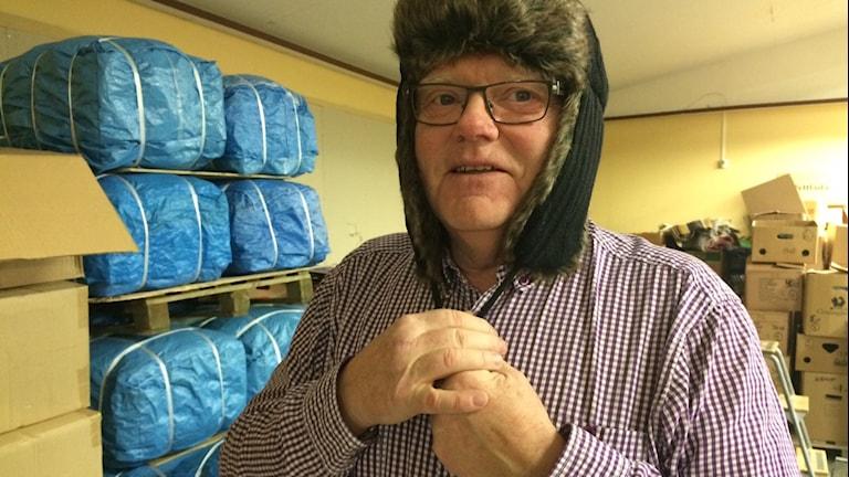Lars-Erik Pehrzon provar mössan som finns med i julklappen till Riga. Foto: Agneta Sundberg/Sveriges Radio