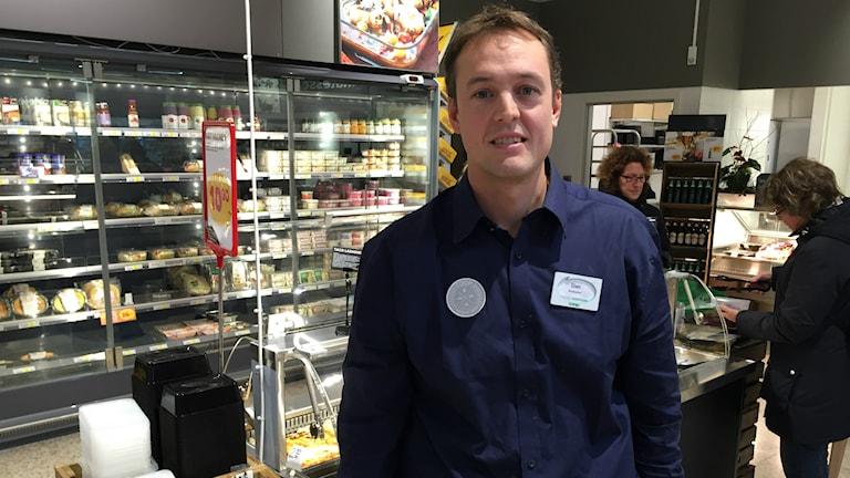 Dan Eklund, butikschef, står framför montern med plockmat.
