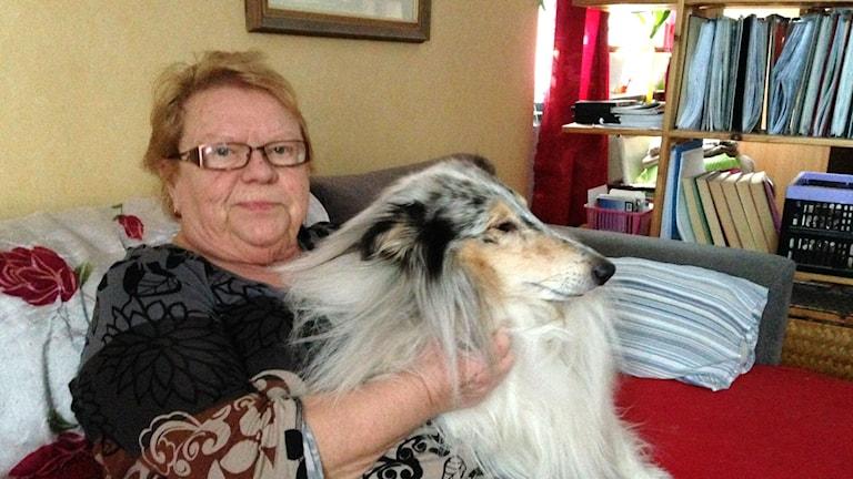 Arja Rohlin sitter i soffan tillsammans med sin hund. Foto: Julia Burman Görans/Sveriges Radio