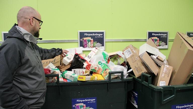 Per Sundström lägger tillbaka en pappersförpackning som åkt ned på golvet. Papper i papper, var sak har sin plats. Foto: Fredrik Björkman/Sveriges Radio