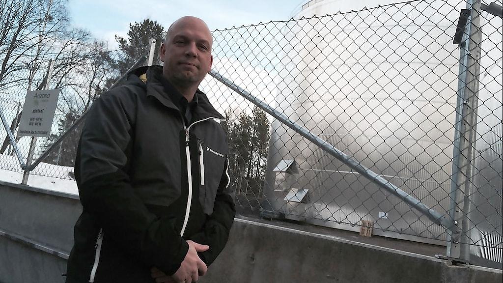 Arizona Chemicals VD Patrik Jakobsson framför de nya cisternerna och den meterhöga betonginvallningen. Foto: Christian Höijer/Sveriges Radio