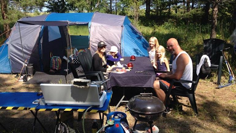 Familj på 5 personer sitter vid sitt tält på Rullsands Campingområde