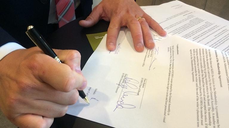 Jörgen Edsvik skriver på kontraktet med ICORN. Foto: Cassandra Alm / Sveriges Radio