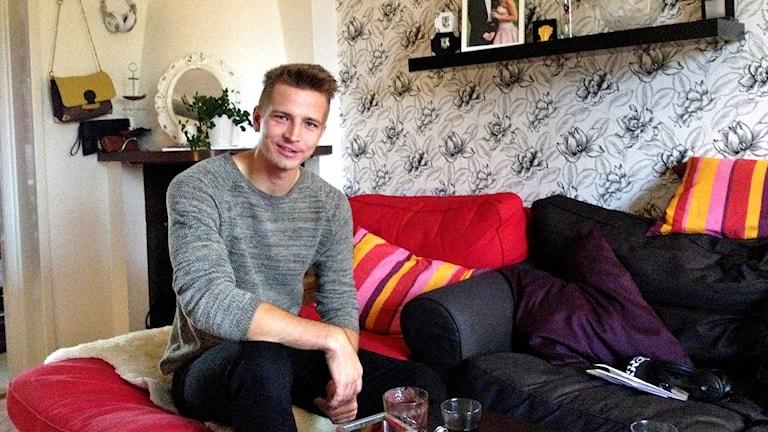 Joel Groth sitter i en soffa i sitt hem.