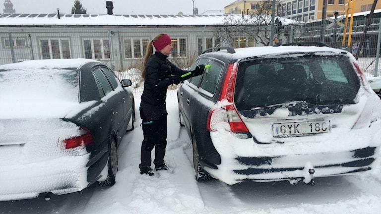 Tjej som skrapar bilrutorna. Foto: Hasse Persson/Sveriges Radio