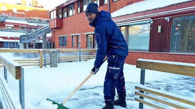Abdi Fatah Adan skottar snö i jobbet som bovärd. Foto: Anna Molin/Sveriges Radio