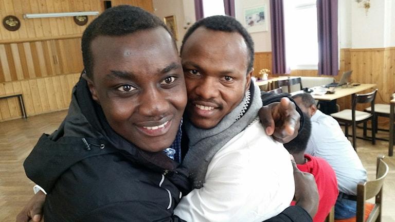 Darfur United-spelarna Yusef Mahamat Abdallaha och Mohammed Adam Abdallah kramar om varandra efter beskedet att de får stanna i Sverige.