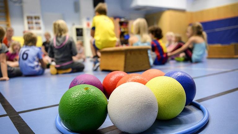 Barn som sitter i en gymnastiksal med bollar och rockring i förgrunden.