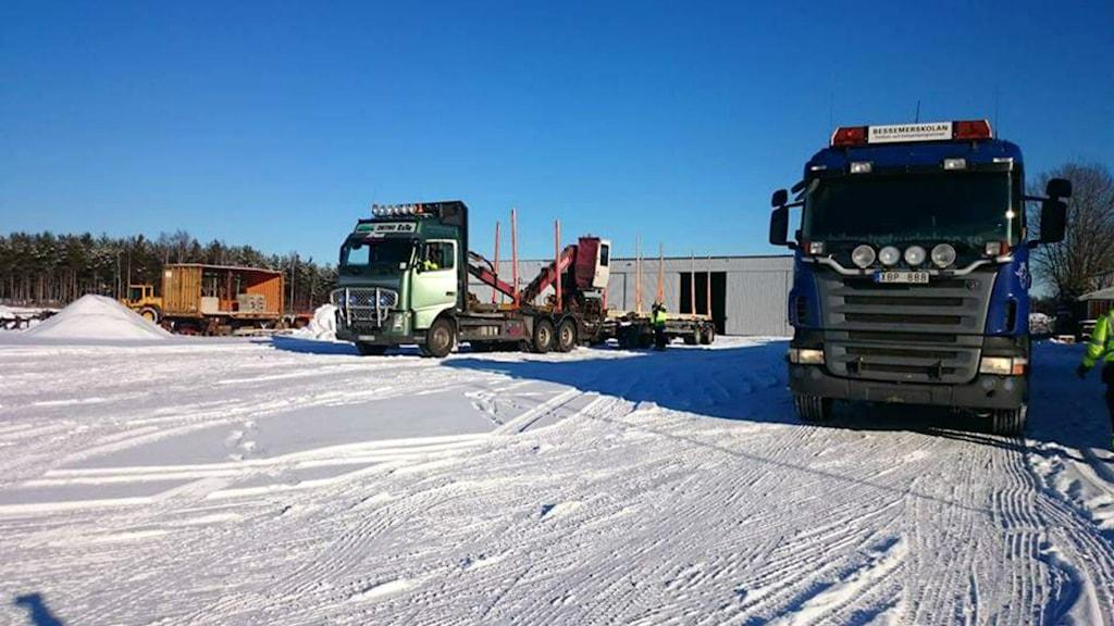 Två lastbilar i vinterlandskap utanför fordonsprogrammets lokaler