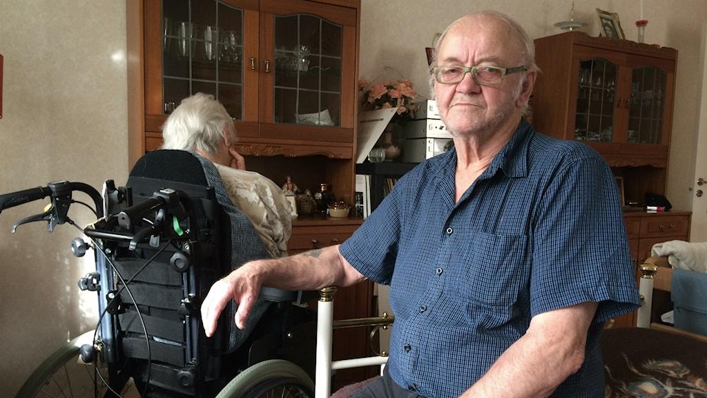 Bror Andersson sitter i sängen i deras lägenhet och Kerstin Östling bredvid, bakåtvänd i sin rullstol.