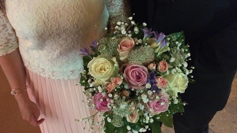 Bröllopspar håller i brudbuketten.