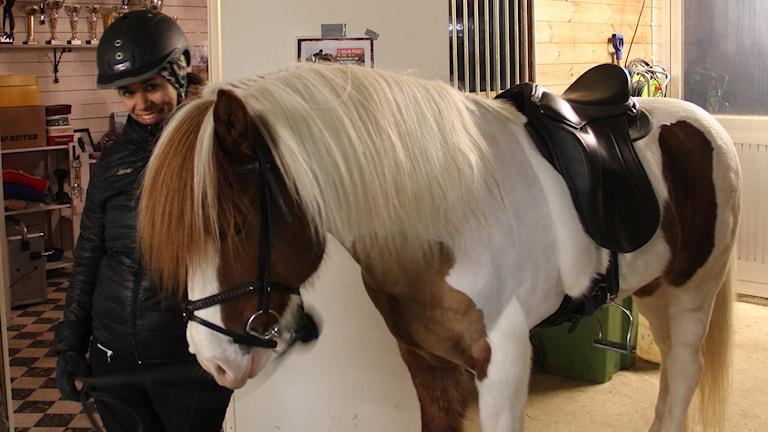 Ryttare står bredvid sin häst i stallet.