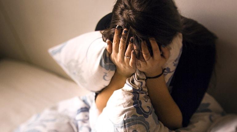 en ledsen ensam tjej med mörkt hår som sitter i en säng och håller för ansiktet med händerna