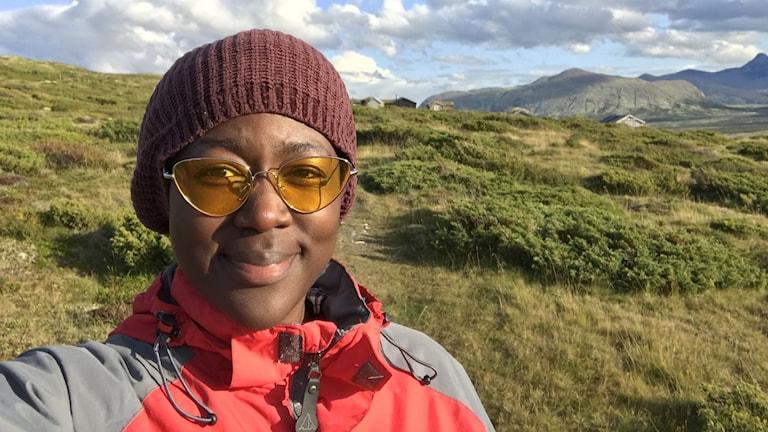 Nelly Aroka, projektledare för Geologins dag och kommunikatör vid myndigheten Sveriges Geologiska undersökning framför ett fjäll.