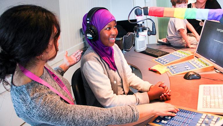 Wenda Hajo, programledare, coachar ett barn från rapatac i hur en kör radio.