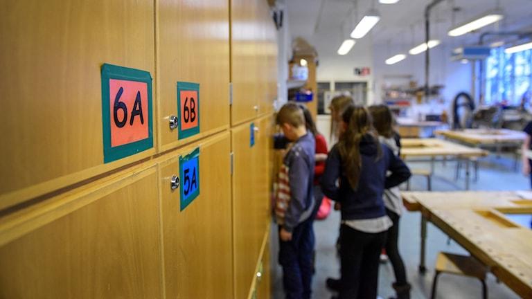 En grupp elever som står i ett klassrum. Barna elevernas ryggar och bakhuvuden syns. I förgrunden syns skåp.