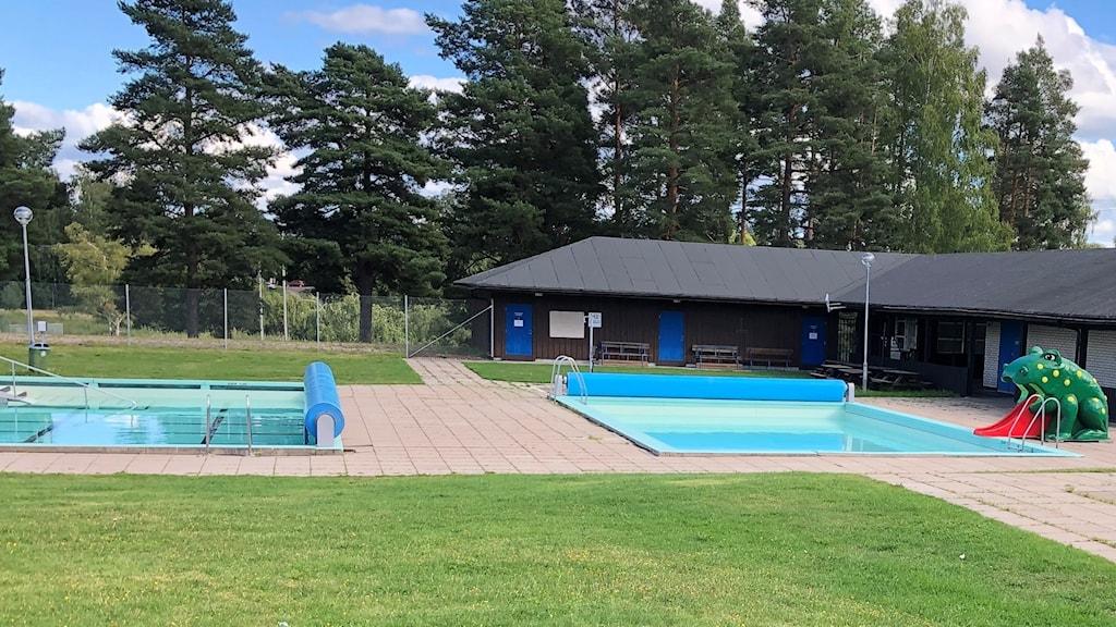 Två pooler och en gräsmatta vid Storviksbadet.