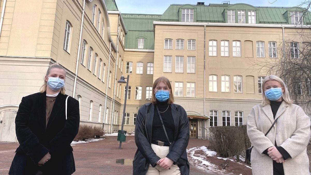 Tre unga kvinnor i munskydd framför en skolbyggnad.